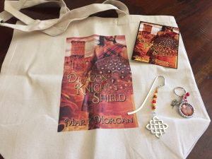 Giveaway: Dragon Knight's Shield Tote, Keychain, Jeweled bookmark, and postcard.